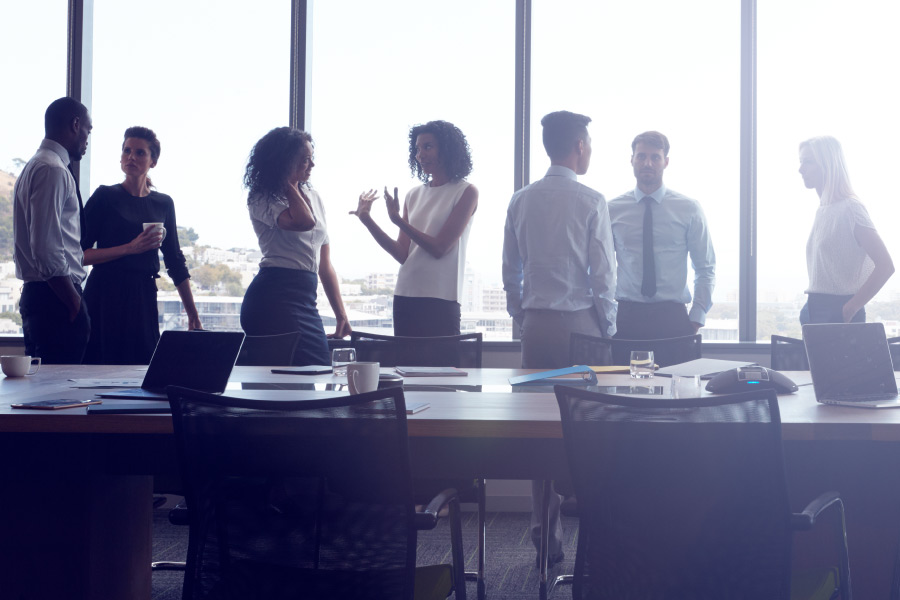 Group of business people stand around talking and discussing business for their career